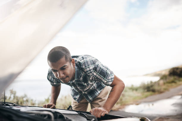 Checking what the problem is Cropped shot of a young man with his broken down car on the side of a road aground stock pictures, royalty-free photos & images