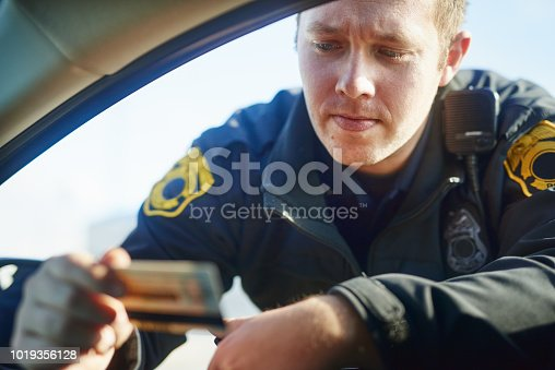 Cropped shot of a handsome young male traffic officer checking a license at a roadblock