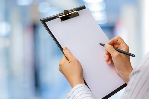 checklist in the hands of a businesswoman . - clipboard stock photos and pictures