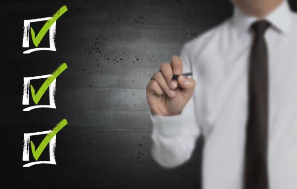 Checkliste wird von Geschäftsmann auf Computerbildschirm geschrieben – Foto