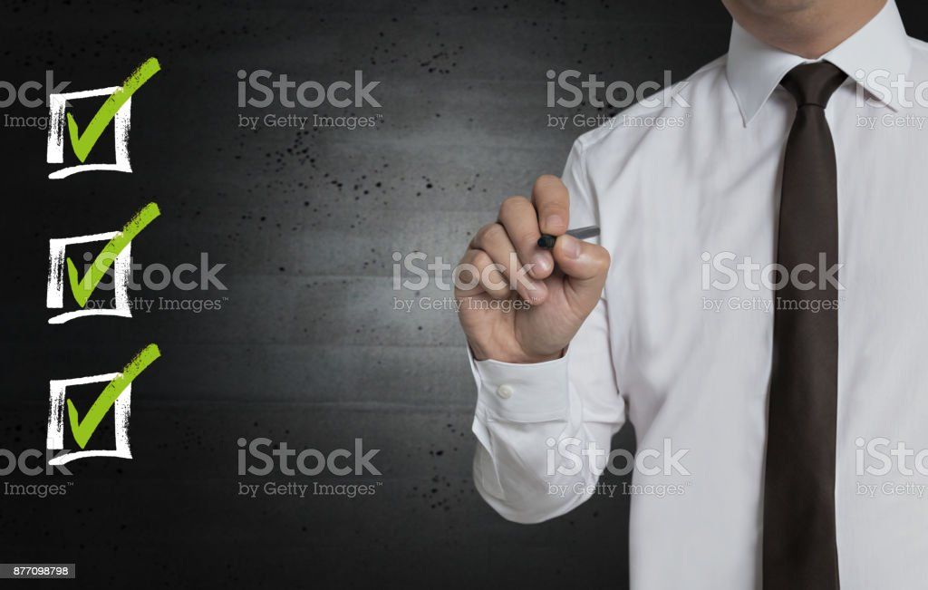 Checklist is written by businessman on screen stock photo