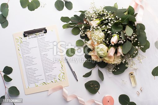 Planning wedding. Checklist with main items, roses bouquet and golden rings on white background