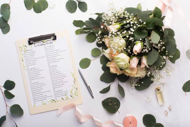 checkliste mit hauptgegenständen, rosenstrauß und goldenen ringen - hochzeit stock-fotos und bilder