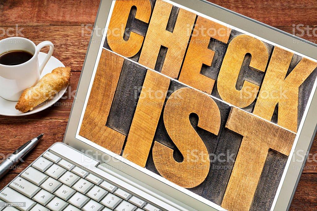 checklist word typography on laptop stock photo