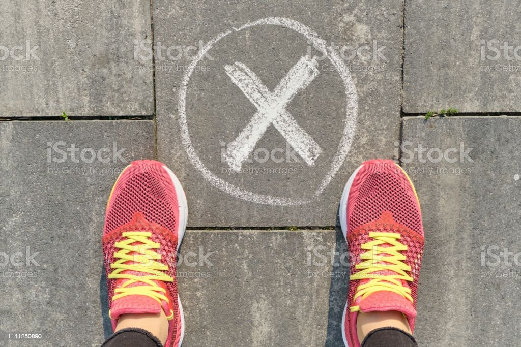 Checkmark no sign on gray sidewalk with woman legs in sneakers, top...