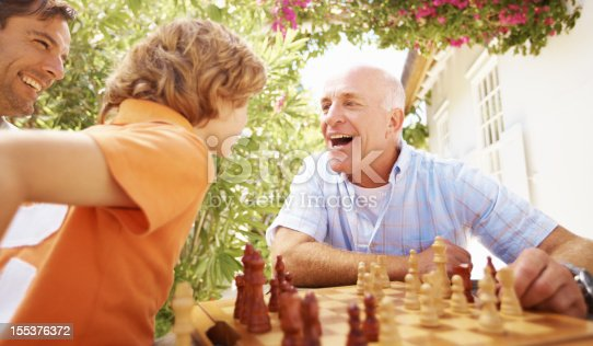 Young boy sitting and playing chess with his grandfather while outdoors