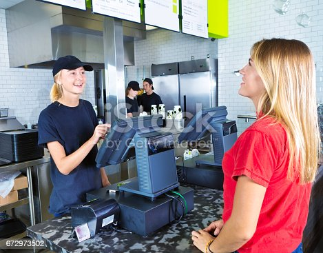 A young woman customer placing her order at a fast food convenience restaurant. A young woman server staff is assisting her at the checkout cashier counter with the kitchen staff working in the background.
