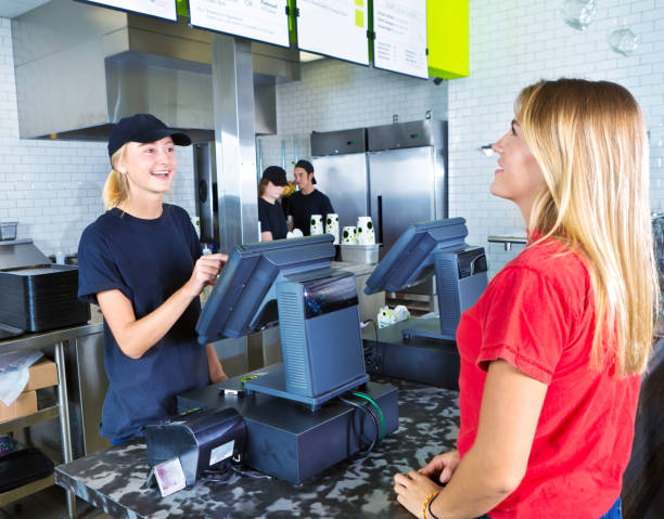 checkout server serving young woman customer ordering at fast food restaurant - fast food restaurant stock pictures, royalty-free photos & images