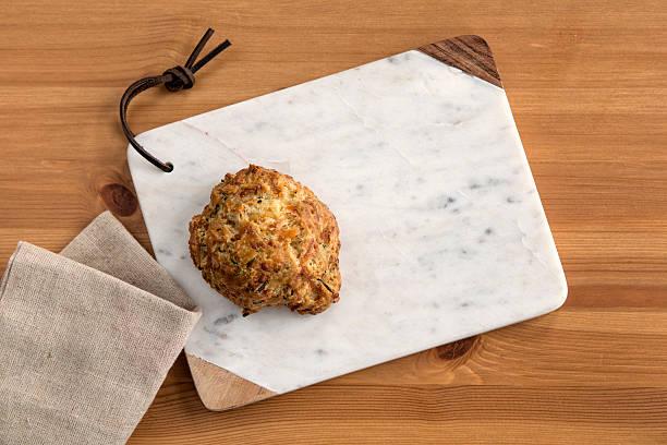 cheddar biscuit on a marble serving board with a napkin - kräuterfaltenbrot stock-fotos und bilder
