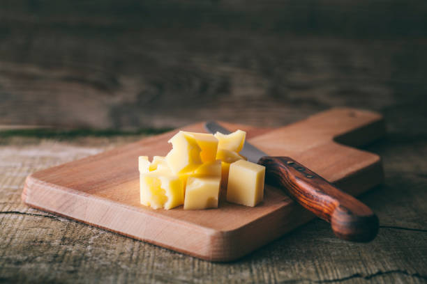 Cheddar cheese, knife, board stock photo