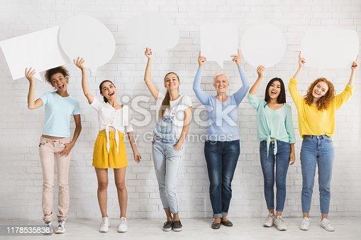 istock Cheeful Women Holding Blank Speech Bubbles Against White Brick Wall 1178535836