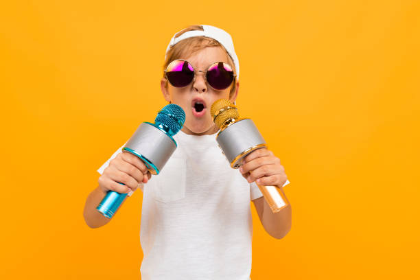 Cheeky blond boy in glasses with two microphones on a yellow background stock photo