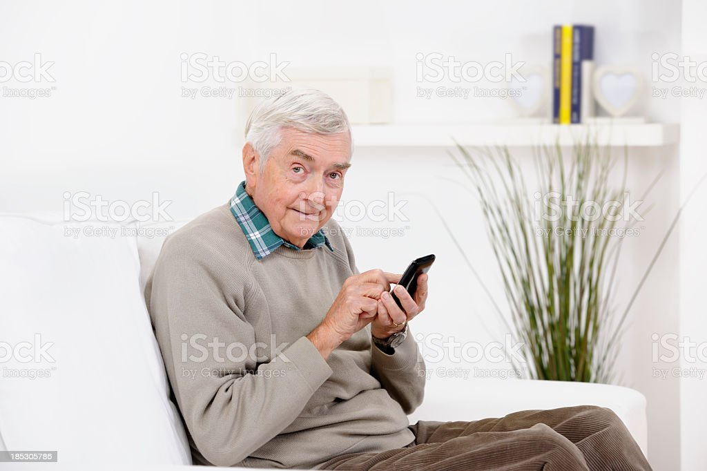 Cheeky Looking Senior Man Using A Mobile/ Smart Phone stock photo