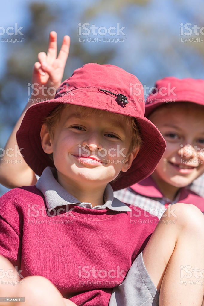 Cheeky School Children doing Rabbit Ears Sign stock photo