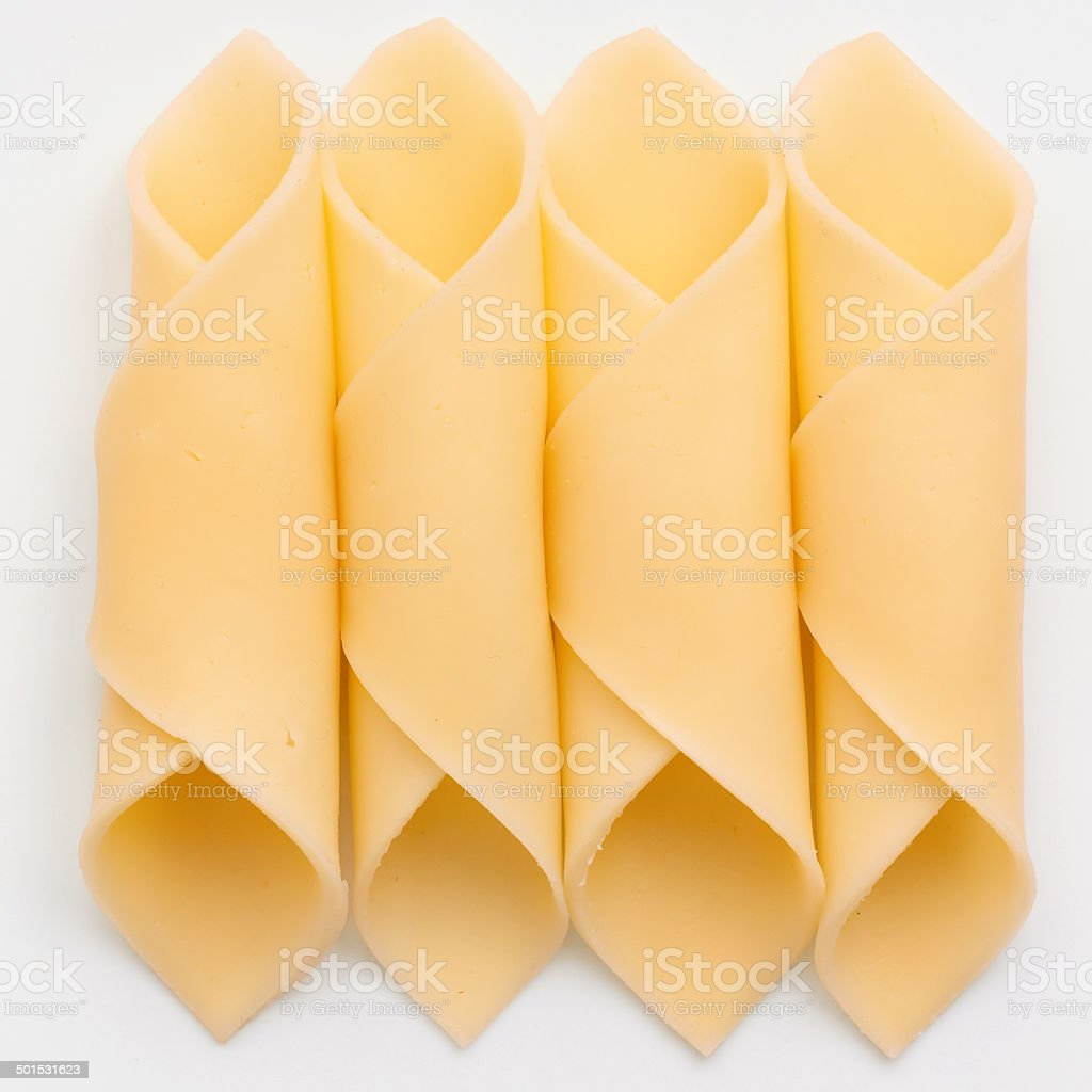 Cheelse slices neatly rolled up on a white surface. stock photo