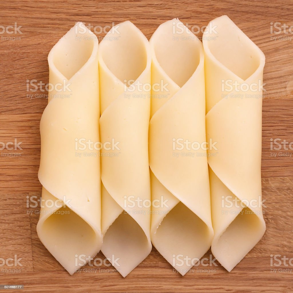 Cheelse slices neatly rolled up on a wood surface. stock photo