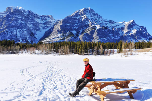 Cheerful 66 years old caucasian senior adult  sitting on a bench  in the Canadian Rockies Cheerful senior man wearing sunglasses and a  sheepskin hat ,is  having a rest on a bench during a hike in the Kananaskis Country, Alberta,Canada. kananaskis country stock pictures, royalty-free photos & images
