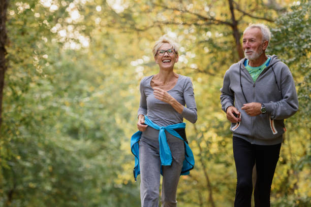 Cheerful active senior couple jogging in the park in the morning Cheerful active senior couple jogging in the park. Exercise together to stop aging. active seniors stock pictures, royalty-free photos & images
