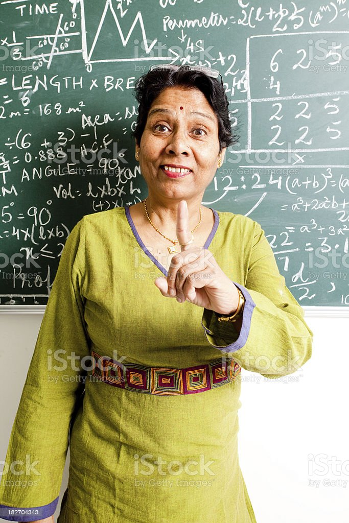 Cheerful Active Senior Indian Mathematics Teacher in a Classroom royalty-free stock photo