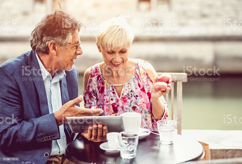 Cheerful adult couple at the coffee bar using digital tablet stock photo