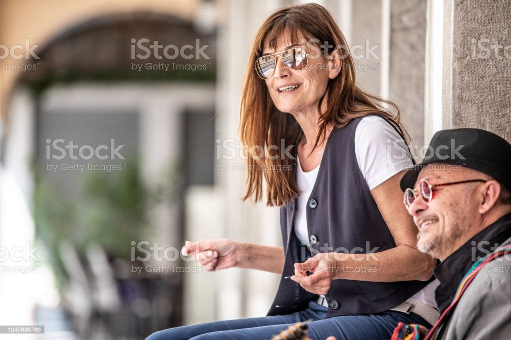 Cheerful Adult Woman and Senior Man Playing Music on City Street.