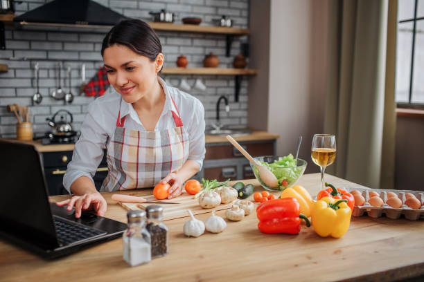 cheerful adult woman sit at table in kitchen. she typing on keyboard and look on screen. woman cook food. - woman cooking stock pictures, royalty-free photos & images