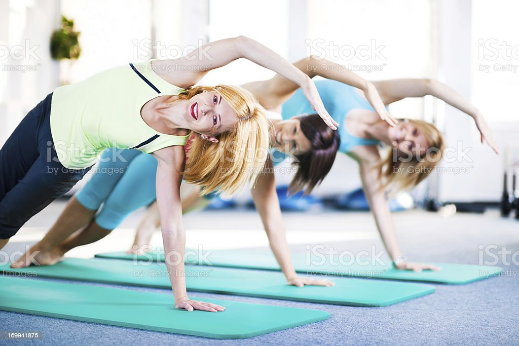 Cheerful adult women doing stretching exercises on Pilates class royalty-free stock photo