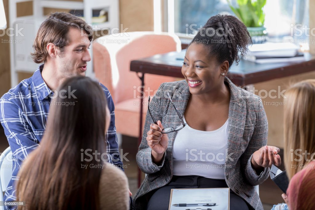 Cheerful African American businesswoman leads meeting stock photo