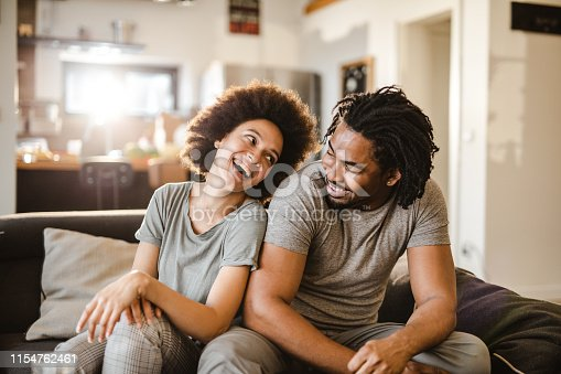 Cheerful black couple having fun while talking on sofa at home.