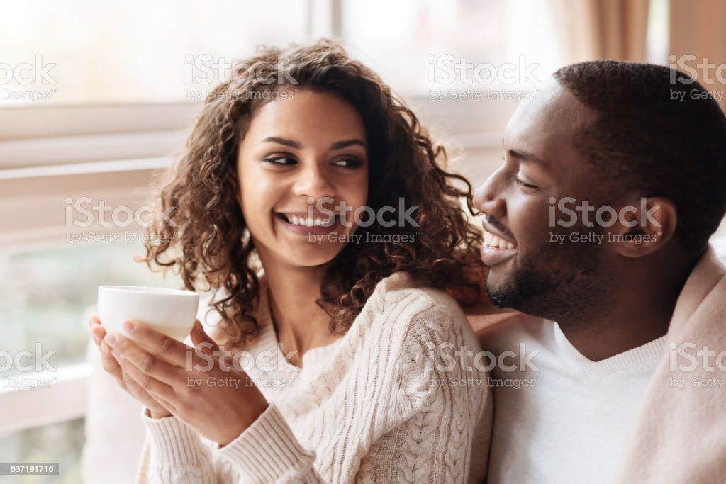 Cheerful African American couple enjoying tea in the cafe - foto de stock
