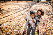 Above view of happy black couple having fun while piggybacking in autumn day at the park. Copy space.