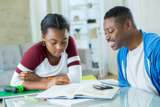 fröhliche african american dad hilft tochter mit mathe-hausaufgaben - haushaltsbuch führen stock-fotos und bilder