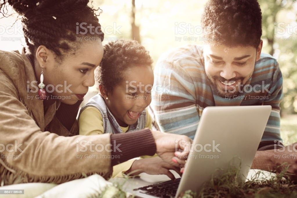 Cheerful African American family lying down in park and  using laptop. royalty-free stock photo