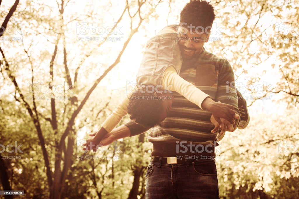 Cheerful African American father in park carrying daughter on shoulders. royalty-free stock photo