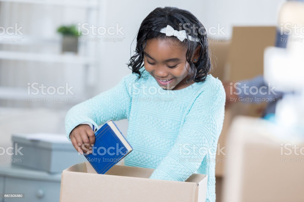 Cheerful African American girl packs books in cardboard box stock photo