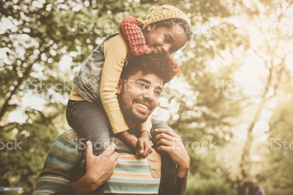 Cheerful African American girl sitting on father shoulders and enjoying in park. royalty-free stock photo