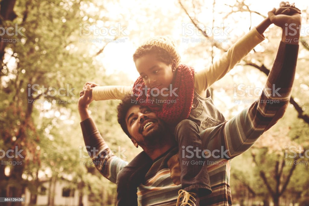 Cheerful African American little girl sitting on father shoulders in park. royalty-free stock photo