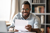 istock Cheerful african american male entrepreneur read great news in letter 1203044172