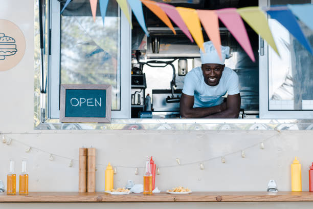 cheerful african american man in chef uniform smiling from food truck cheerful african american man in chef uniform smiling from food truck food truck stock pictures, royalty-free photos & images