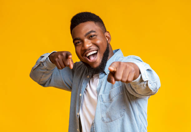 Cheerful african american man pointing fingers at camera Gotcha. Overjoyed black guy pointing fingers at camera over yellow studio background, empty space excited stock pictures, royalty-free photos & images