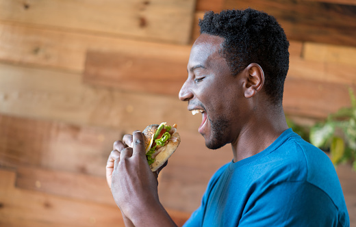 Cheerful african american man starting to eat a delicious sandwich at a cafeteria