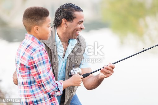 istock Cheerful African American man teaches grandson to fish 619774406