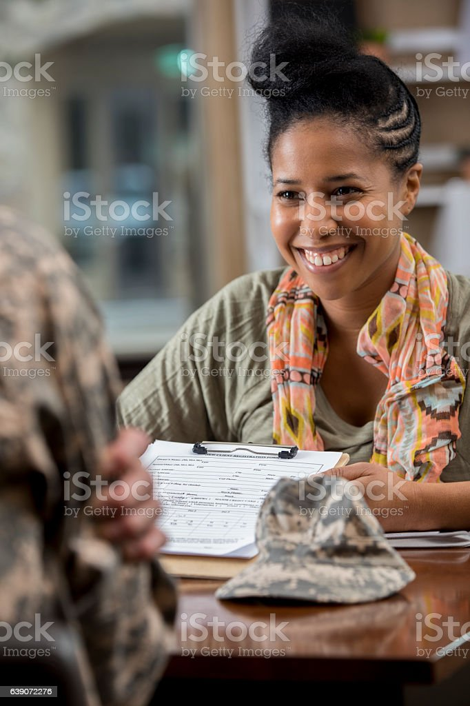 Cheerful African American military counselor helps veteran with paperwork stock photo