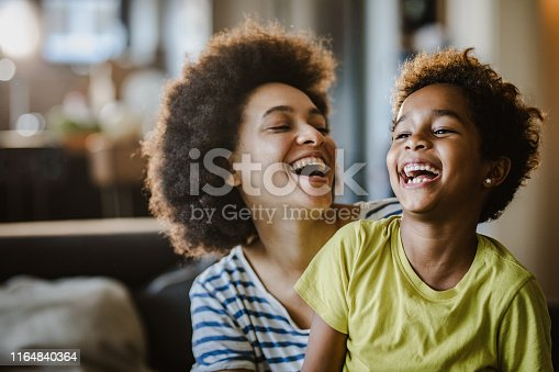 Cheerful black mother and daughter having fun while laughing at home.