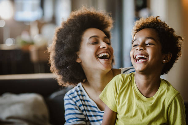 Cheerful African American mother and daughter at home. stock photo