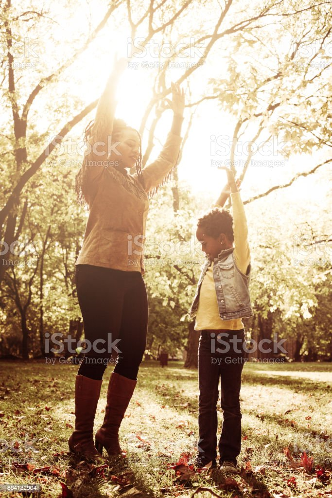 Cheerful African American mother with daughter in playing dancing together. royalty-free stock photo
