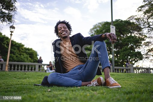 Handsome and fashionable African American hipster spending a sunny day at a city in autumn.