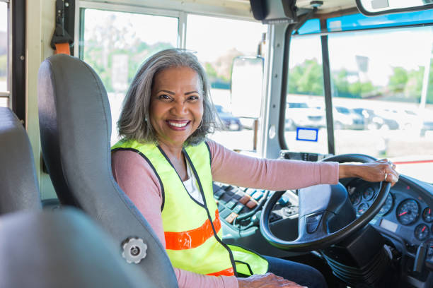 Cheerful African American teacher is also bus driver stock photo