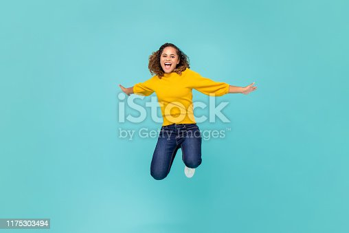 Cheerful African American woman in colorful yellow t-shirt and blue jeans jumping isolated on blue background
