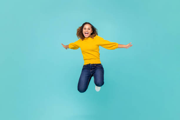 Cheerful African American woman  jumping Cheerful African American woman in colorful yellow t-shirt and blue jeans jumping isolated on blue background background color stock pictures, royalty-free photos & images